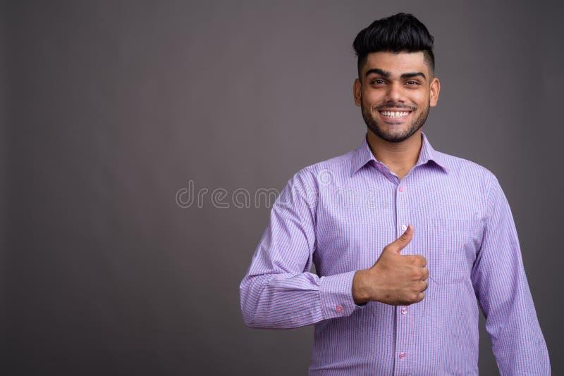 Hombre de negocios indio hermoso joven contra fondo gris foto de archivo libre de regalías