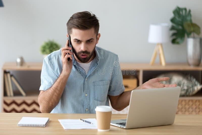Hombre de negocios infeliz ultrajado que habla en el teléfono, conversación desagradable fotografía de archivo