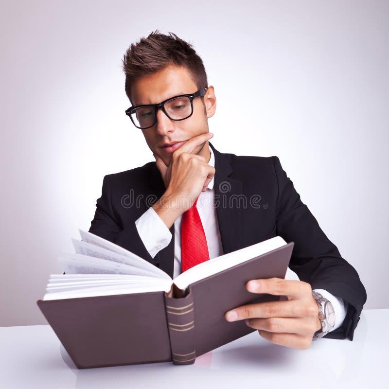 Hombre de negocios intrigante que lee un libro fotografía de archivo