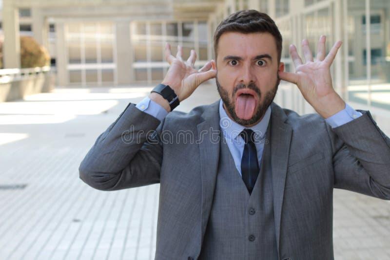 Hombre de negocios irrespetuoso que pega la lengua hacia fuera imágenes de archivo libres de regalías