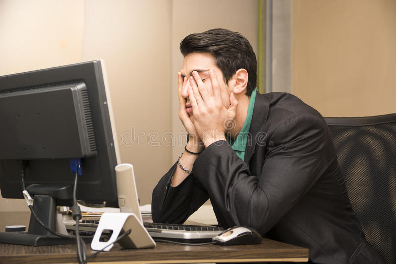 Hombre de negocios joven aburrido cansado en oficina fotos de archivo