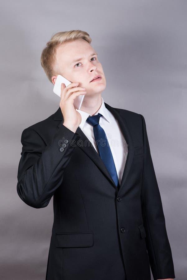 Hombre de negocios joven acertado feliz que se coloca que habla en el teléfono celular, móvil imagen de archivo libre de regalías