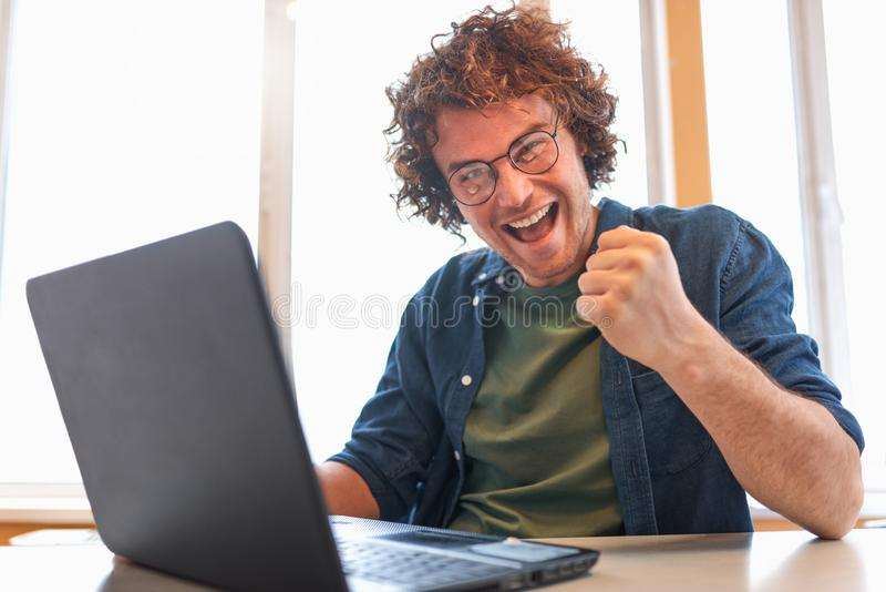 Hombre de negocios joven acertado feliz que usa el ordenador portátil en su escritorio de oficina que hace gesto del ganador fotos de archivo libres de regalías