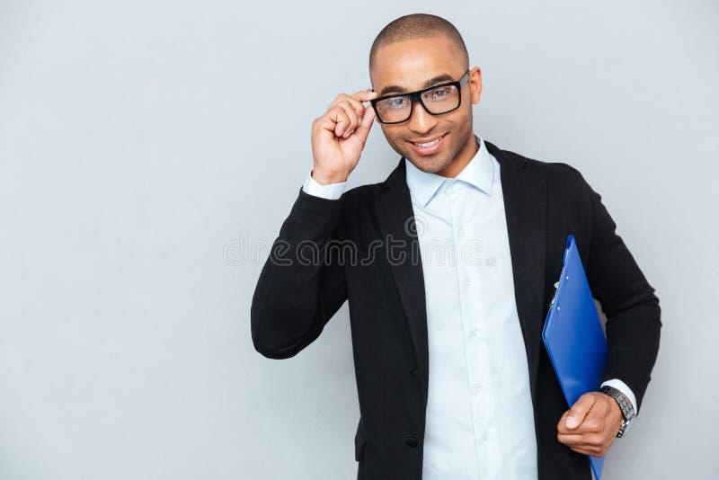 Hombre de negocios joven africano alegre en vidrios con la carpeta azul imagen de archivo libre de regalías