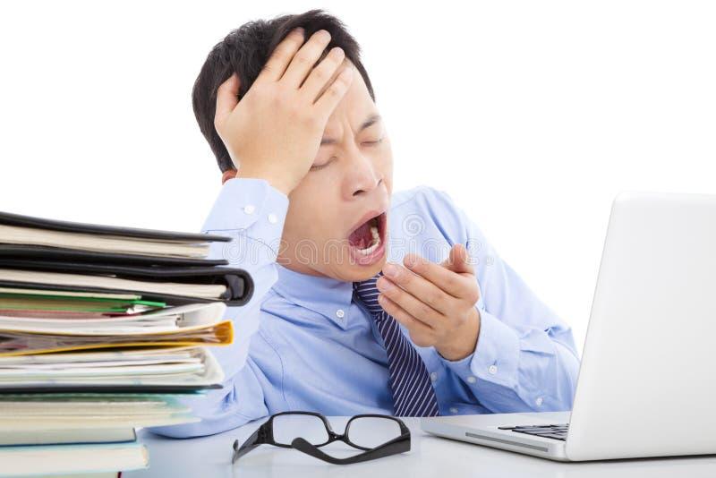 Hombre de negocios joven agotado que bosteza y que lleva a cabo su cabeza imagen de archivo libre de regalías