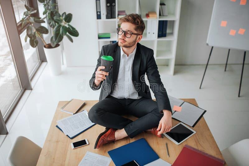 Hombre de negocios joven agradable si en actitud del loto en la tabla en sitio Él bebe el café y la mirada en la ventana Calma de imagenes de archivo