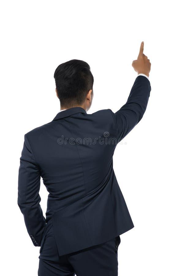 Hombre de negocios joven aislado que señala, visión trasera imagen de archivo