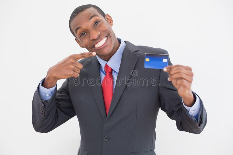 Hombre de negocios joven alegre del Afro que señala en la tarjeta de crédito imagenes de archivo