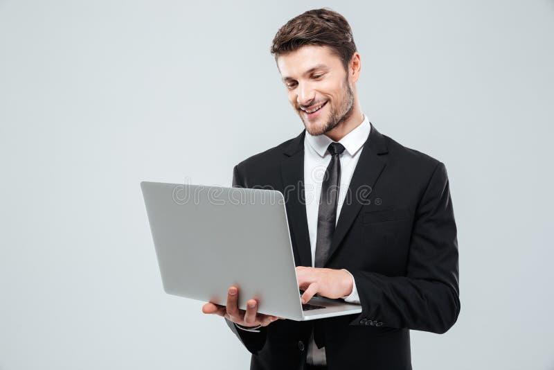 Hombre de negocios joven alegre que sonríe y que usa el ordenador portátil imagen de archivo