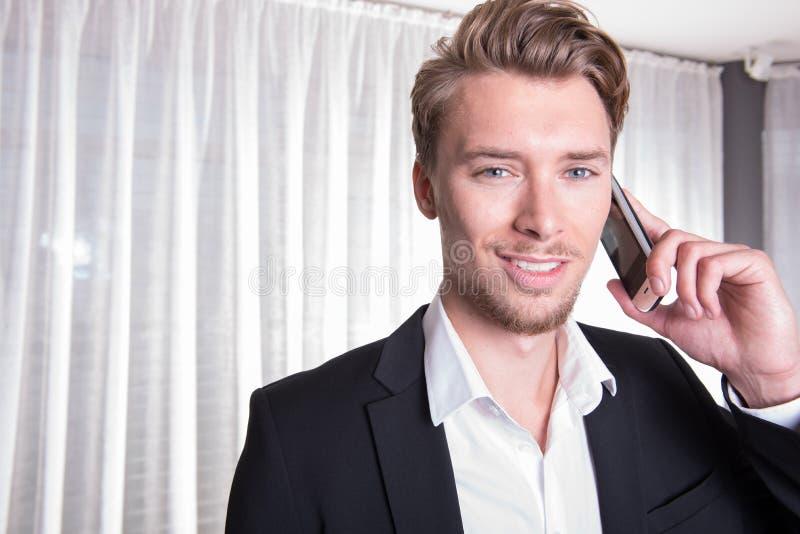 Hombre de negocios joven amistoso del retrato en traje en el teléfono fotografía de archivo libre de regalías