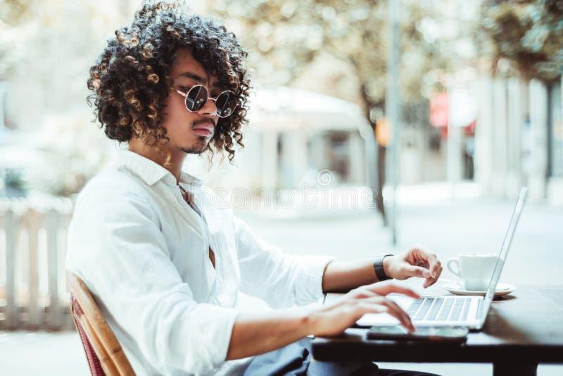 Hombre de negocios joven asiático con el ordenador portátil en un café al aire libre fotografía de archivo