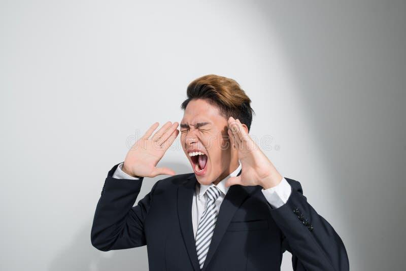 Hombre de negocios joven asiático en traje negro clásico que grita hacia fuera ruidosamente imagen de archivo libre de regalías