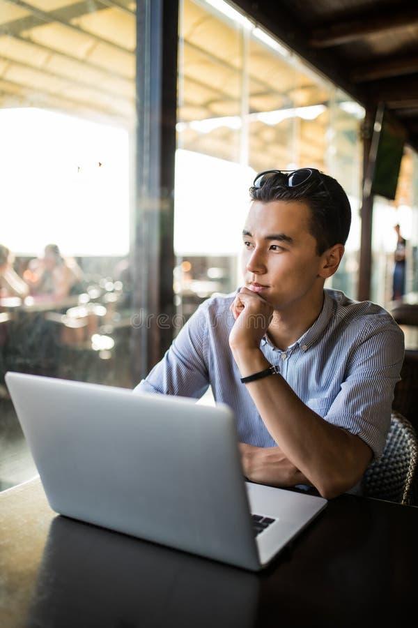 Hombre de negocios joven asiático que trabaja con el ordenador portátil en el café de la ciudad Trabaja independientemente el tra fotos de archivo libres de regalías