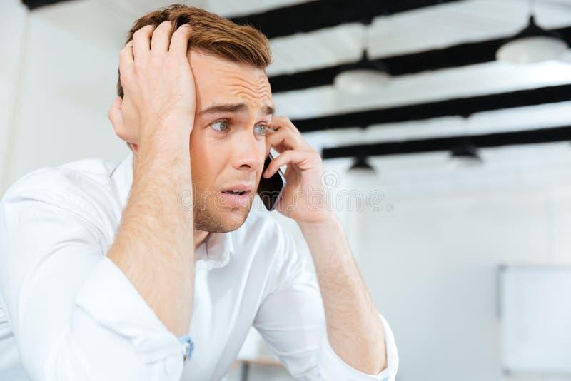 Hombre de negocios joven asombroso pasmado que habla en el teléfono celular fotos de archivo libres de regalías