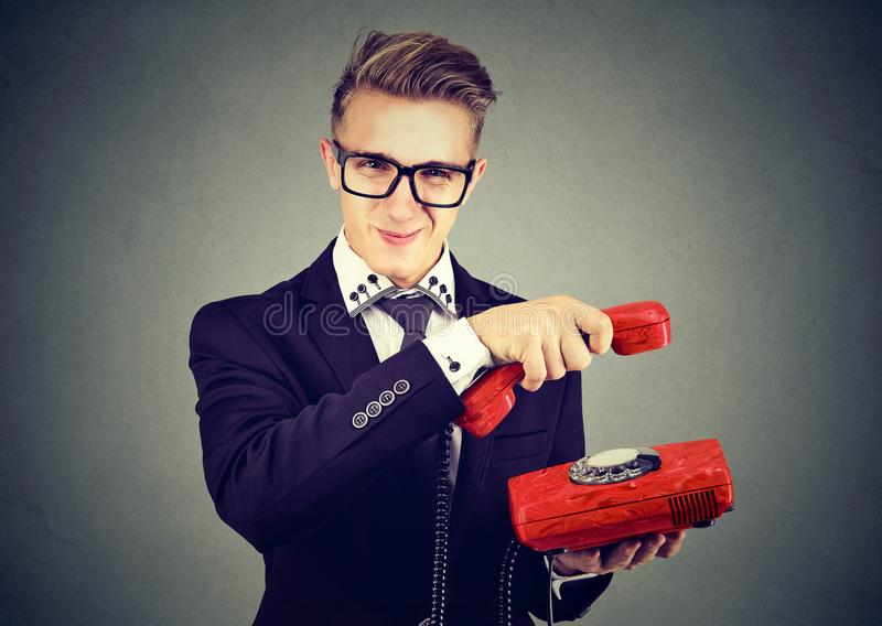 Hombre de negocios joven astuto enfadado que cuelga para arriba el teléfono imagen de archivo