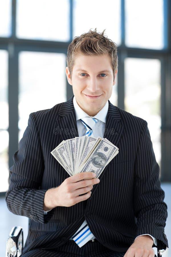 Hombre de negocios joven atractivo que muestra dólares fotos de archivo