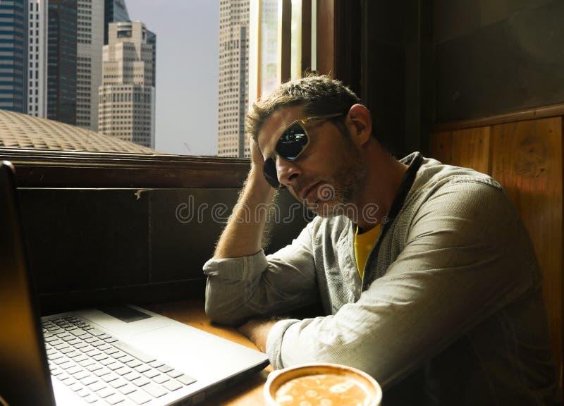 Hombre de negocios joven atractivo y acertado joven que trabaja relajado de cafetería de Internet con el ordenador portátil pensa imágenes de archivo libres de regalías