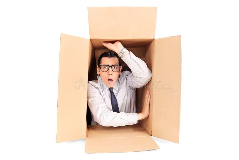 Hombre de negocios joven atrapado en una caja foto de archivo
