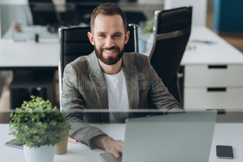 Hombre de negocios joven barbudo que trabaja en la oficina moderna Sirva la camisa blanca que lleva y las notas de la fabricaci?n fotografía de archivo
