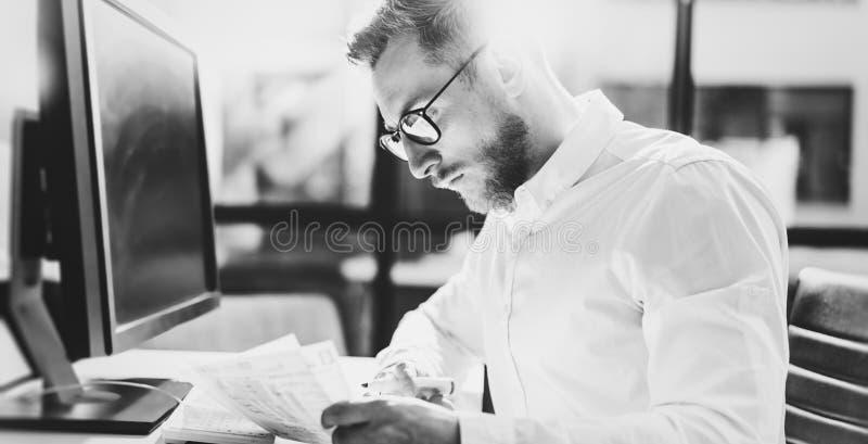 Hombre de negocios joven barbudo que trabaja en la oficina moderna Sirva la camisa blanca que lleva y las notas de la fabricación imágenes de archivo libres de regalías