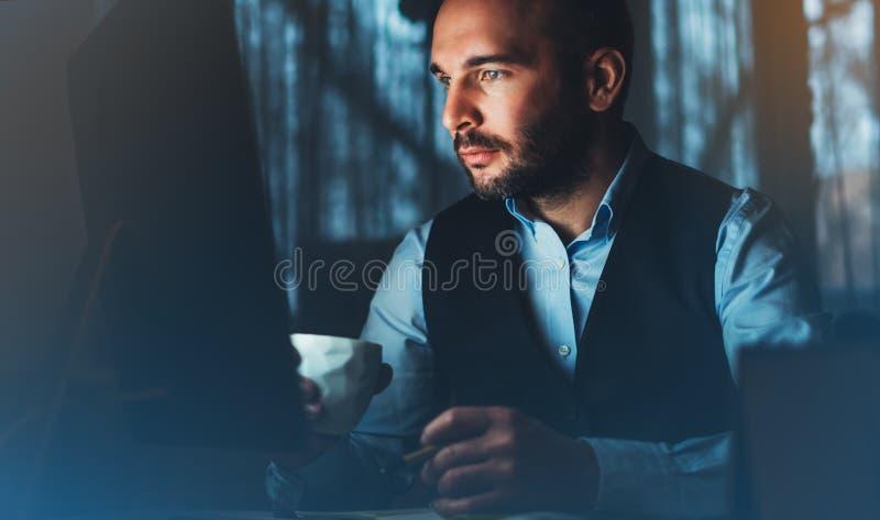 Hombre de negocios joven barbudo que trabaja en oficina moderna Mirada de pensamiento del hombre del consultor en ordenador del m imagen de archivo libre de regalías