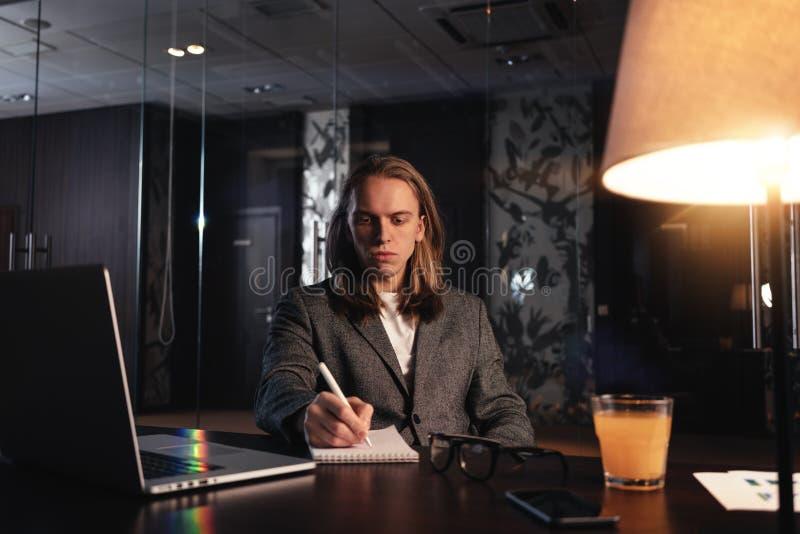Hombre de negocios joven cansado con el pelo largo que trabaja en el estudio coworking moderno de la noche El hombre se sienta po imagen de archivo