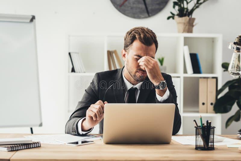 hombre de negocios joven cansado que se sienta en el lugar de trabajo imagen de archivo
