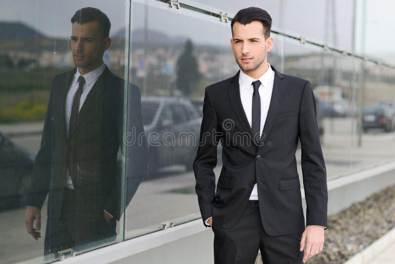 Hombre de negocios joven cerca de un edificio de oficinas imágenes de archivo libres de regalías