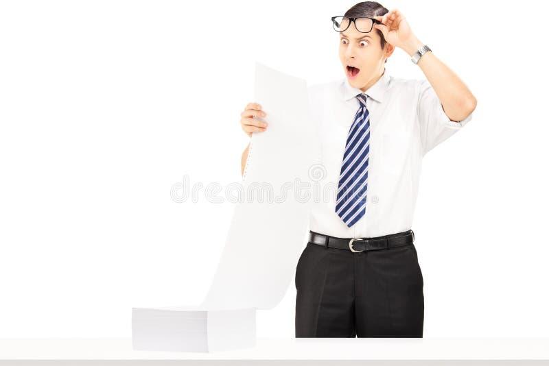 Hombre de negocios joven chocado que lee un documento imagenes de archivo