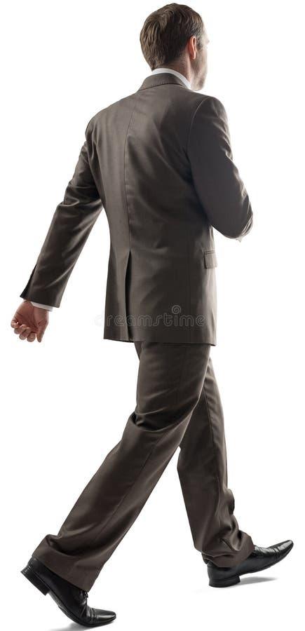 Hombre de negocios joven con caminar corto del pelo oscuro foto de archivo libre de regalías