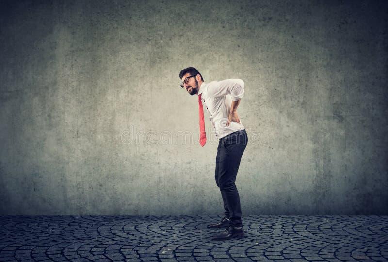 Hombre de negocios joven con dolor de espalda en fondo gris fotos de archivo libres de regalías
