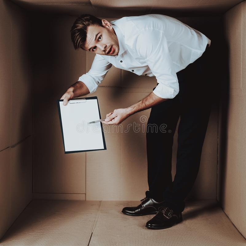 Hombre de negocios joven con el cuaderno en caja de cartón foto de archivo libre de regalías