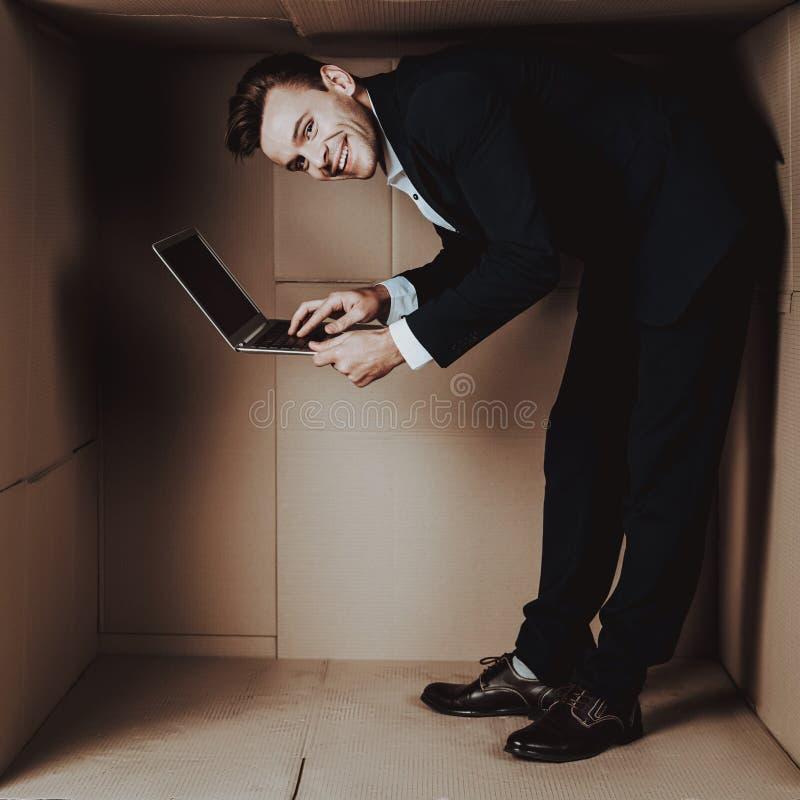 Hombre de negocios joven con el ordenador portátil en caja de cartón fotos de archivo libres de regalías