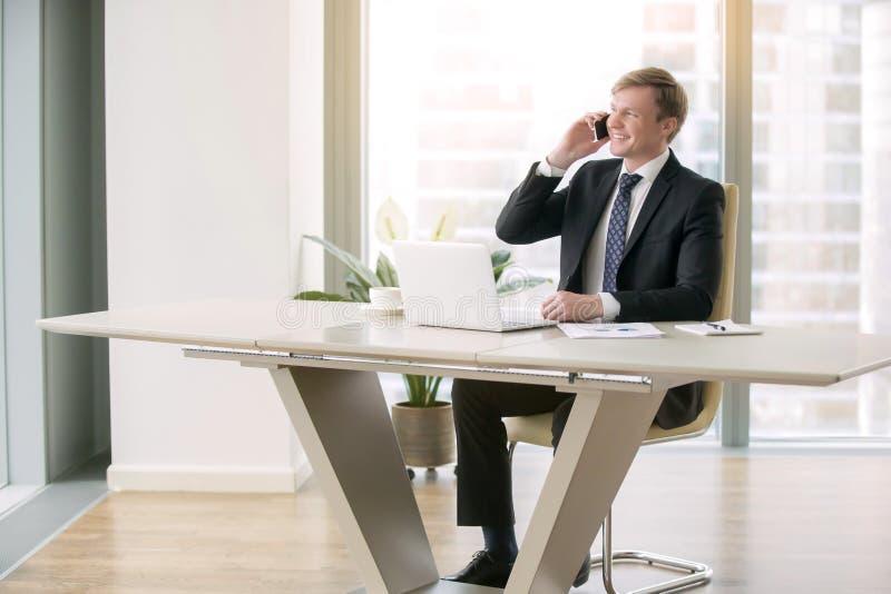 Hombre de negocios joven con el ordenador portátil en el escritorio moderno foto de archivo libre de regalías