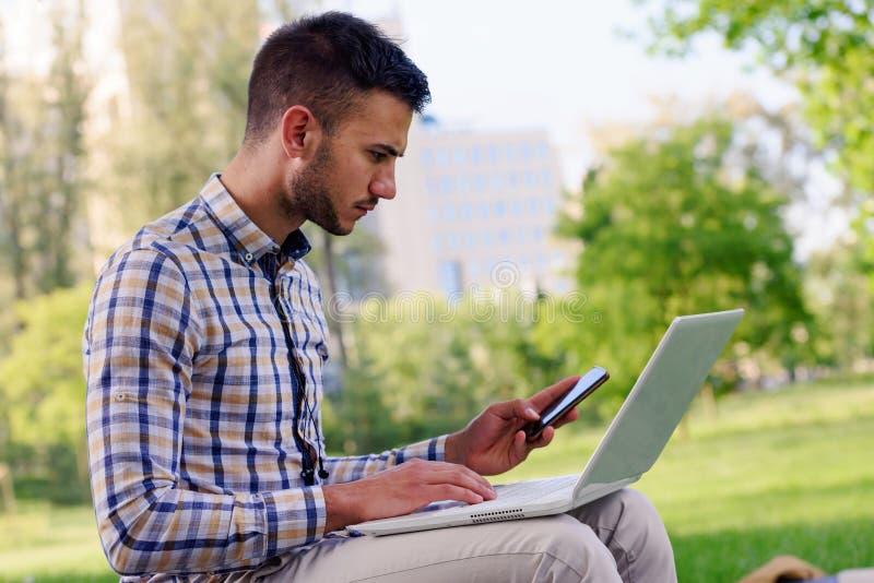 Hombre de negocios joven con el ordenador portátil que trabaja en el parque cerca del edificio de oficinas imagen de archivo libre de regalías