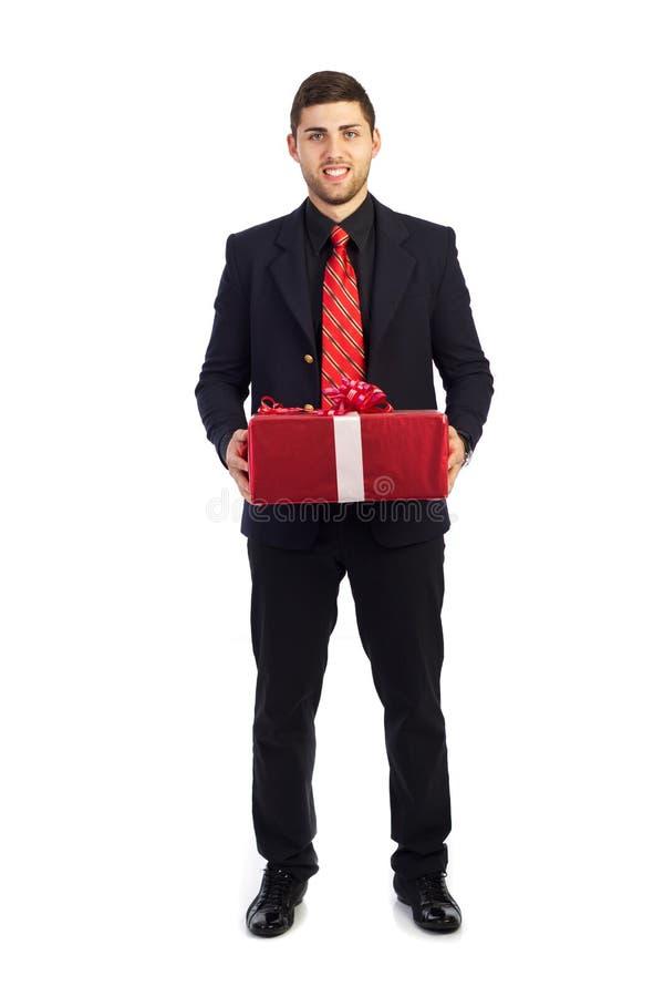 Hombre de negocios joven con el regalo rojo a disposición imagen de archivo libre de regalías
