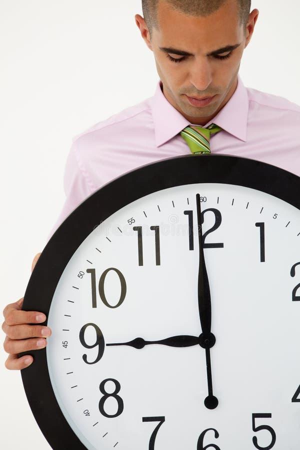 Hombre de negocios joven con el reloj gigante imagen de archivo