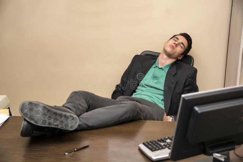 Hombre de negocios joven con exceso de trabajo, cansado que duerme en foto de archivo