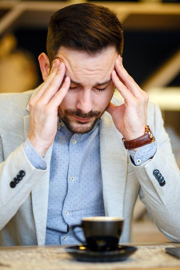 Hombre de negocios joven con exceso de trabajo que tiene un dolor de cabeza y que concentra mientras que bebe una taza de café imagenes de archivo