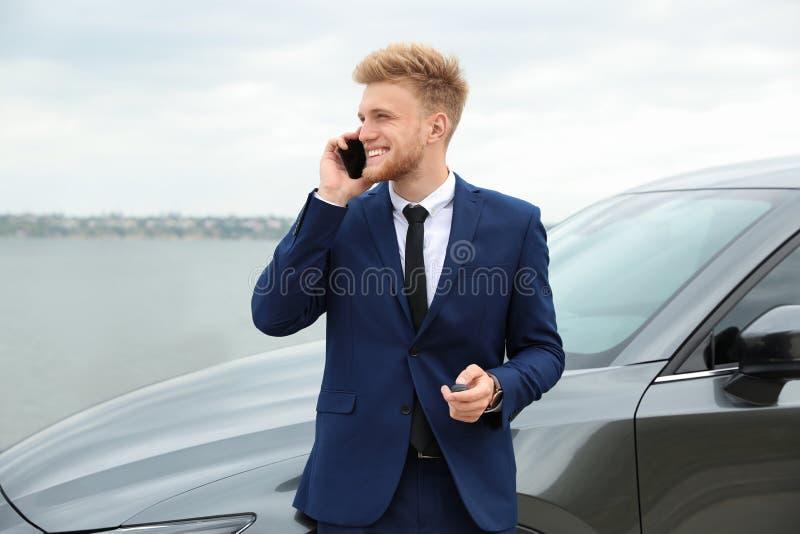 Hombre de negocios joven con hablar dominante en el teléfono cerca del coche imagen de archivo libre de regalías