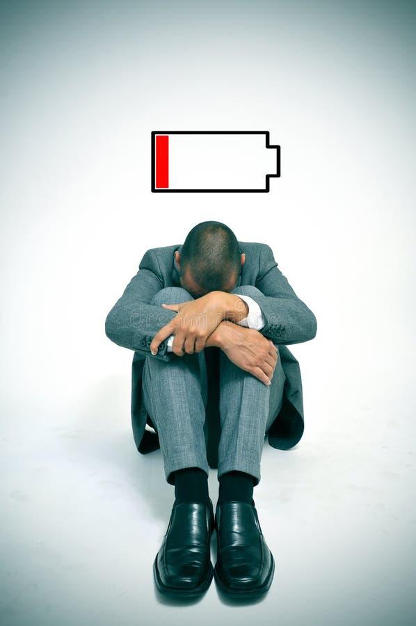 Hombre de negocios joven con la batería baja foto de archivo libre de regalías