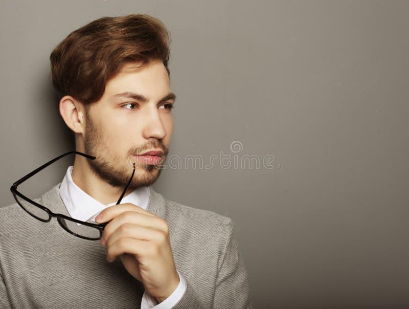 Hombre de negocios joven con las lentes, mirando la cámara contra imagen de archivo libre de regalías