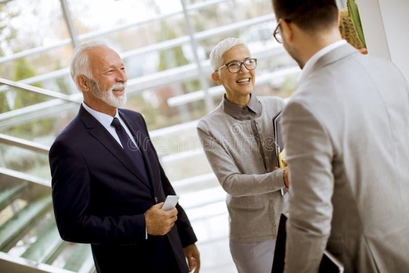 Hombre de negocios joven con los clientes mayores que se colocan en oficina fotografía de archivo libre de regalías