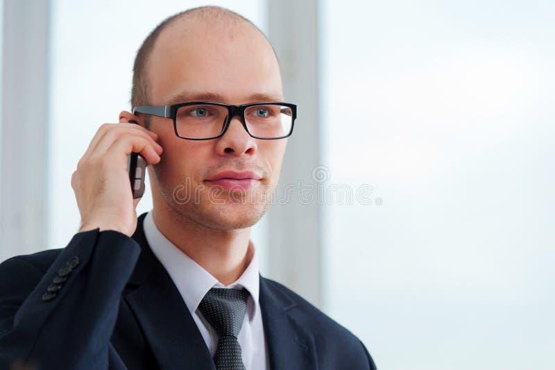 Hombre de negocios joven con los vidrios que habla en el teléfono foto de archivo libre de regalías