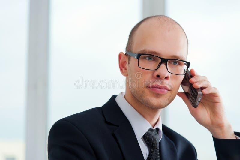 Hombre de negocios joven con los vidrios que habla en el teléfono en oficina fotos de archivo