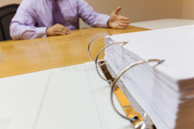Hombre de negocios joven con problemas y la tensión en la oficina que se sienta delante del foco selectivo de la carpeta fotos de archivo