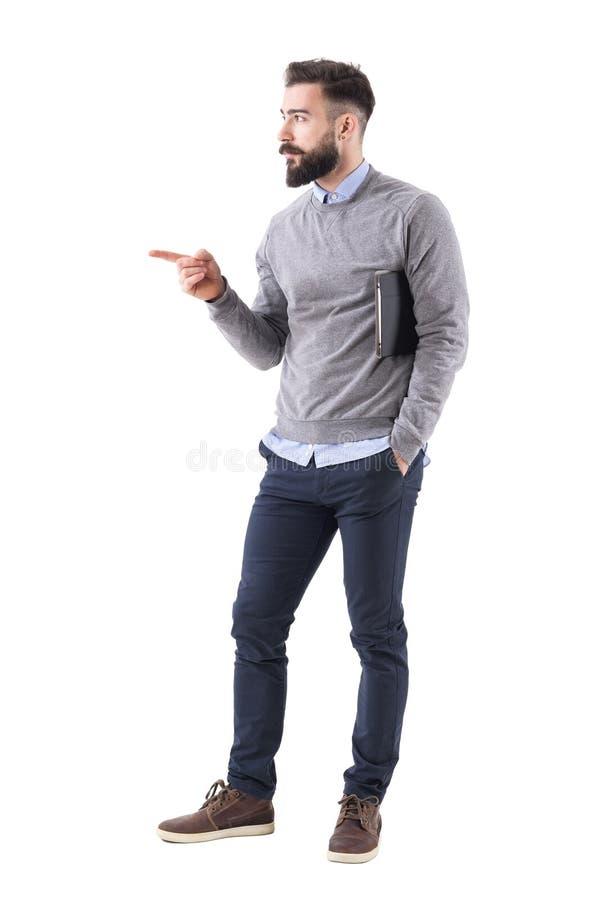 Hombre de negocios joven confiado con los documentos que señala el finger en el copyspace fotografía de archivo libre de regalías