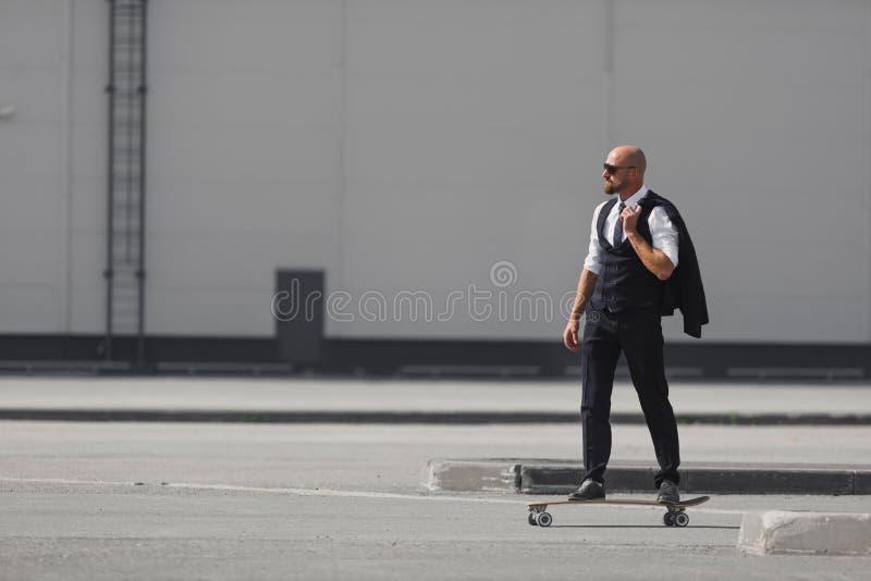 Hombre de negocios joven confiado en traje de negocios en el longboard que se apresura a su oficina, en la calle en la ciudad foto de archivo libre de regalías