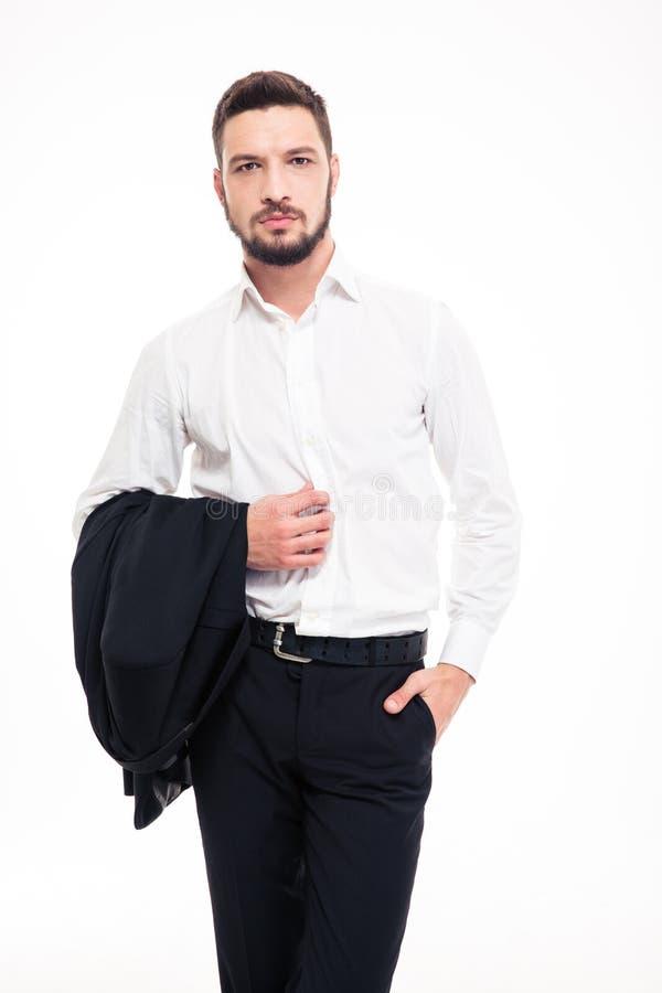 Hombre de negocios joven confiado hermoso con la barba que coloca y que sostiene la chaqueta fotos de archivo libres de regalías