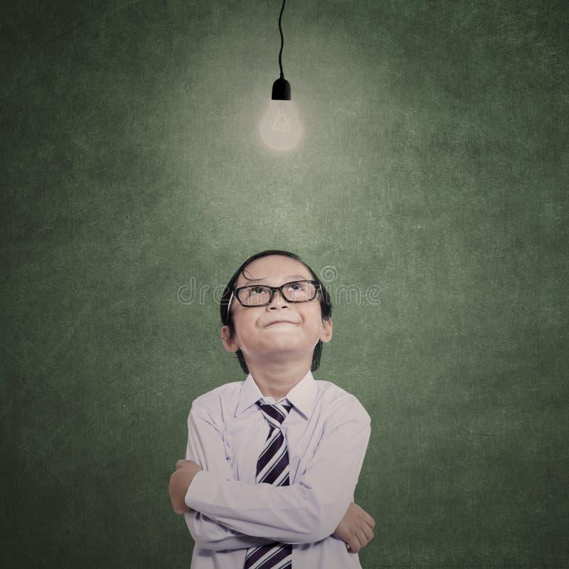 Hombre de negocios joven debajo del bulbo encendido en clase fotos de archivo libres de regalías